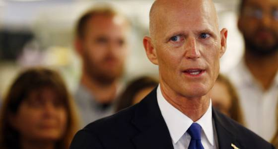 Who is trying to buy access to Rick Scott?